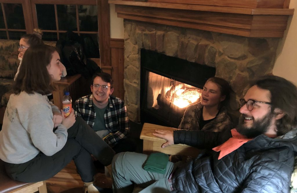 Students relaxing indoors beside a fire at James River State Park.