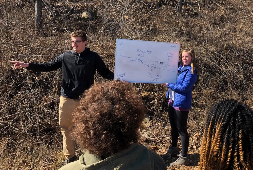 William & Mary geologist makes a point while discussing research in the field, using a white board.