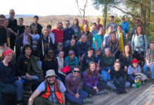 Group photo of 45 William & Mary geology students on a wooden deck at James River State Park with mountains in the distant background