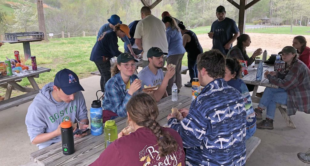 Lunchtime scene of students eating sandwiches and other picnic lunch fare sitting at picnic tables in a covered picnic area.