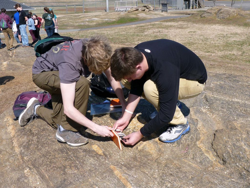 Students measuring a geological structure at Hidden Rock park.