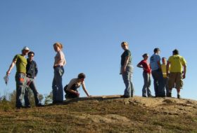 W&M students at Hidden Rock Park, standing atop an outcrop with blue sky behind them.