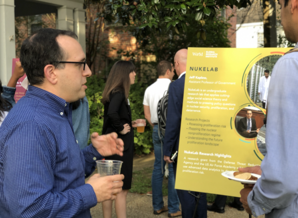 Faculty, staff and students in business casual attire, holding refreshments and discussing research posters on display in the tree-lined front yard of the GRI house.