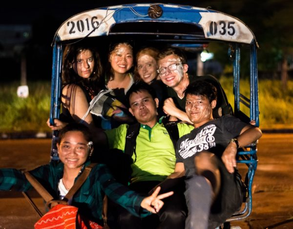 Group of seven people squished in an open air vehicle