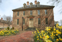 Historic brick building in early spring with bright yellow daffodils in bloom in the foreground.