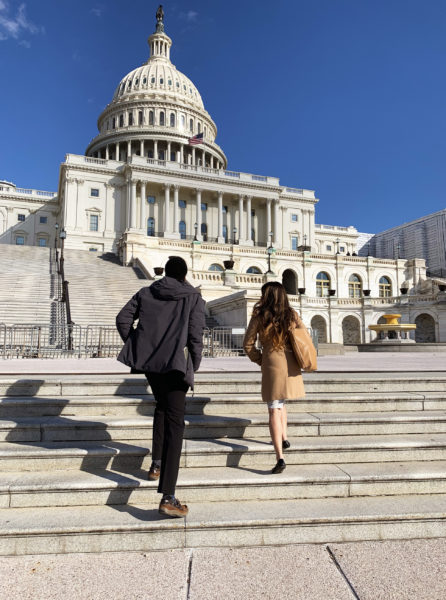 Two students walking up the steps of the Capitol Building in professional attire.