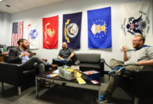 An office space with military flags on the wall and comfortable conversation chairs and couches with two students talking with Charlie Foster
