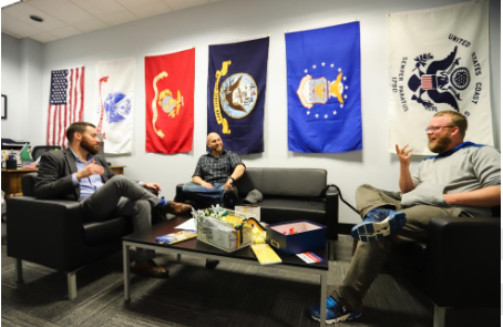 A bright office space with the U.S. and military flags hanging on the wall behind comfortable conversation chairs and couches with two students smiling and talking with Charlie Foster