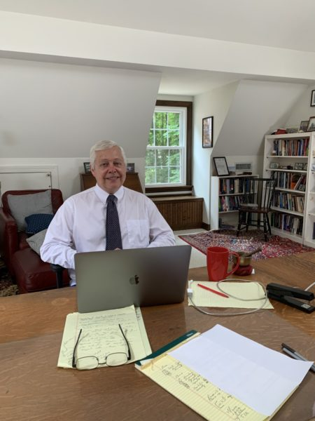 Professor Larry Evans in a shirt an tie in front of an open laptop with papers and notes round on a large table.