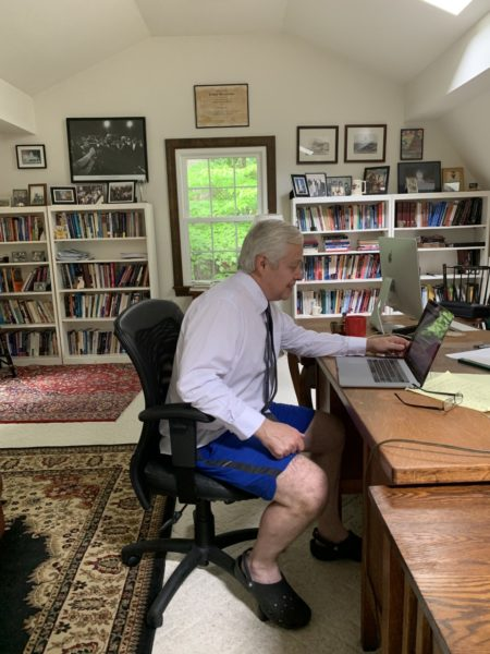 Professor Evans sitting at his desk on Zoom in front of a laptop wearing a shirt and tie, and casual shorts and shoes.
