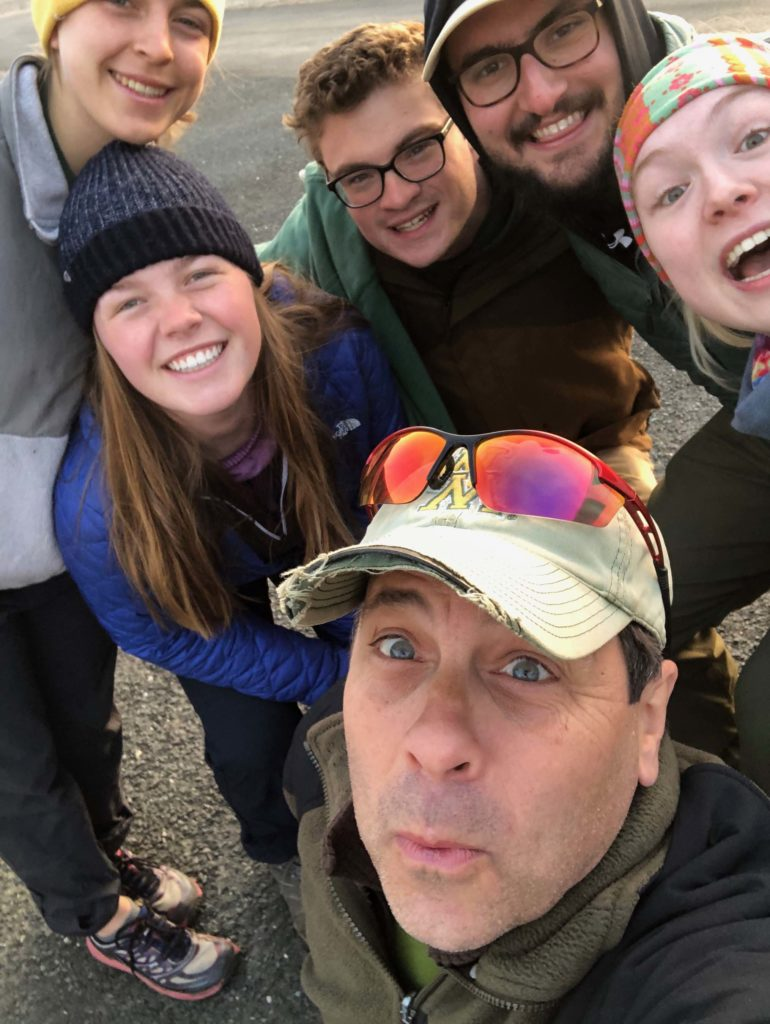 Five students and Professor Bailey posing for the camera with smiles in outdoor gear.