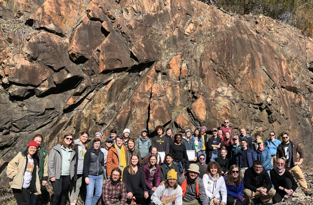 Group of about 40 W&M students in front of a large outcrop.