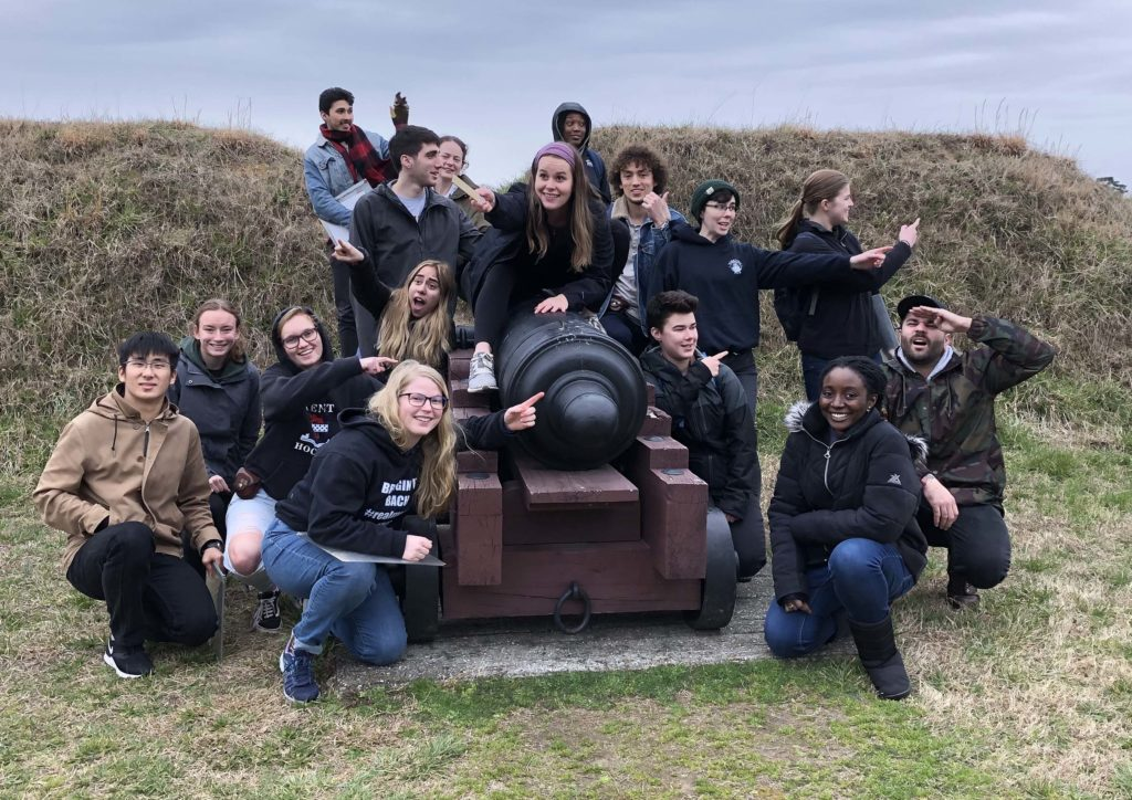 W&M students posing around a cannon at the Yorktown Battlefield, with several pointing off in one direction.