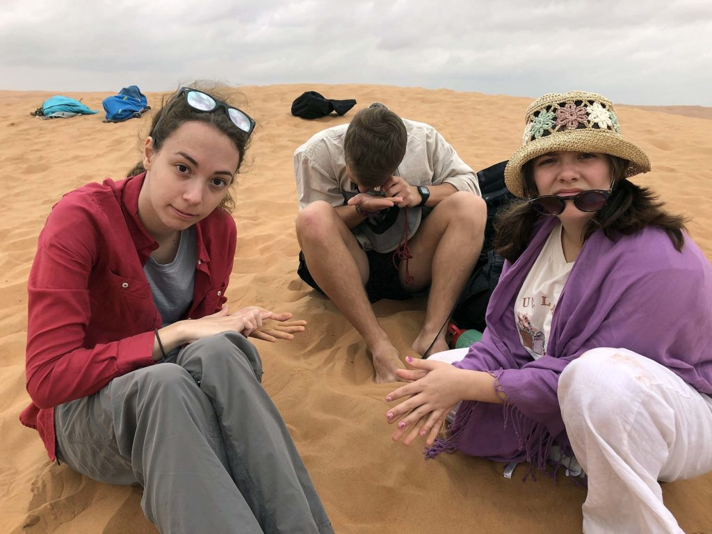 W&M students examining sand on a dune.