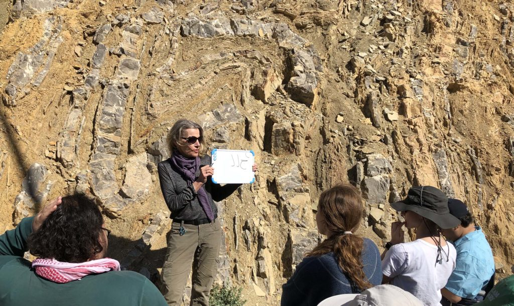Professor Rasmussen lectures at an outcrop, holding a small white board.