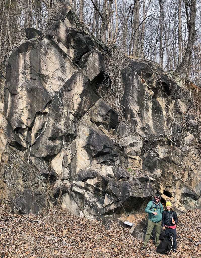 Two people and a dog posed in front of a rock outcrop.