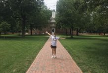 A person standing with arms outstretched joyfully on the brick pathway leading through grass and trees to the historic Wren Building on campus.