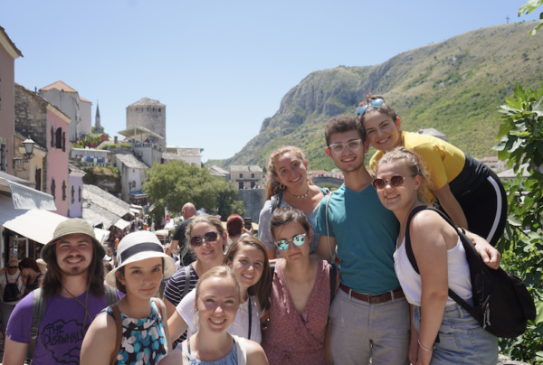A group of 10 students in hats and sunglasses posed and smiling in front of steep hills and a town.