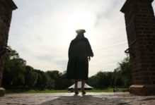A silhouette of a graduate in commencement robes and mortar board standing at the top of the steps to the Sunken Garden