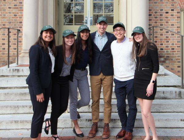 Group of six posed on the stone steps of a brick building, in matching PIPS hats.