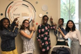 Group of five students smiling and pointing to a collage installation of circles on a wall, surrounding the Global Research Institute's circular logo.