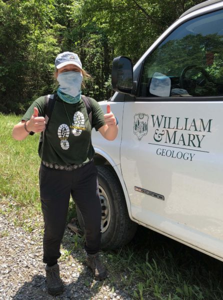 W&M geologist in outdoor gear and face covering giving two thumbs up next to a W&M Geology truck.