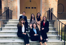 Seven students in business attire on the steps of the Wren Building