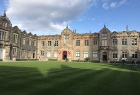 Expansive green lawn leading up to old stone buildings of St Andrews.