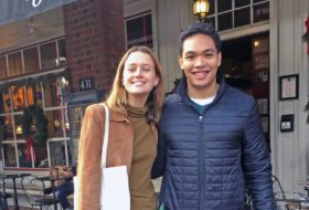 Two students posed and smiling out front of Aroma's Cafe in Williamsburg, VA.
