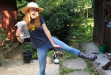 Margaret wearing black spotted rain boots and a straw hat posing in her yard.