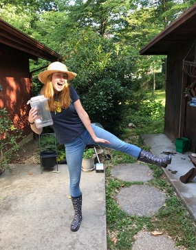 A person wearing black spotted rain boots and a straw hat posing with a smile in her yard.