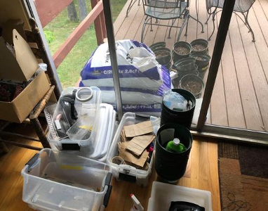 A series of materials such as clear plastic bins, paper bags, dirt, and pots in Margaret's dining room.