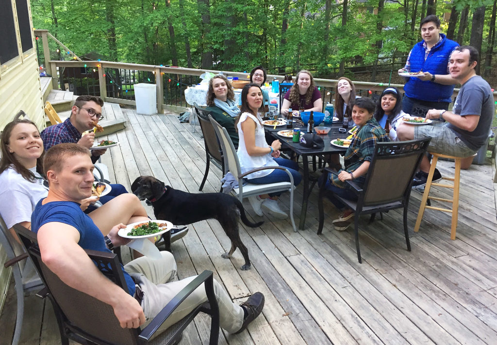 Twelve W&M geologists having a picnic around a table on a large deck.