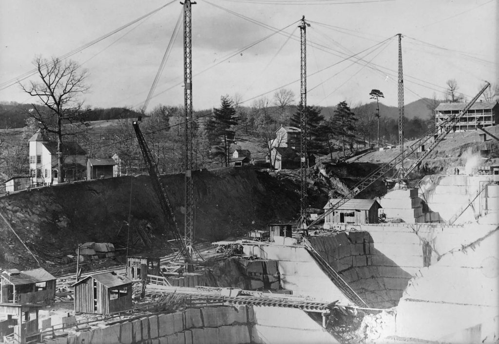 Black and white photo of closely neighboring rock quarries with small buildings, tracks and cranes around their perimeters