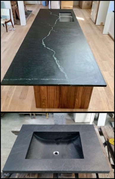 Black soapstone countertop and sink displayed in a showroom.