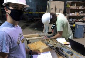 Two W&M researchers in masks and hard hats examining rock cores.