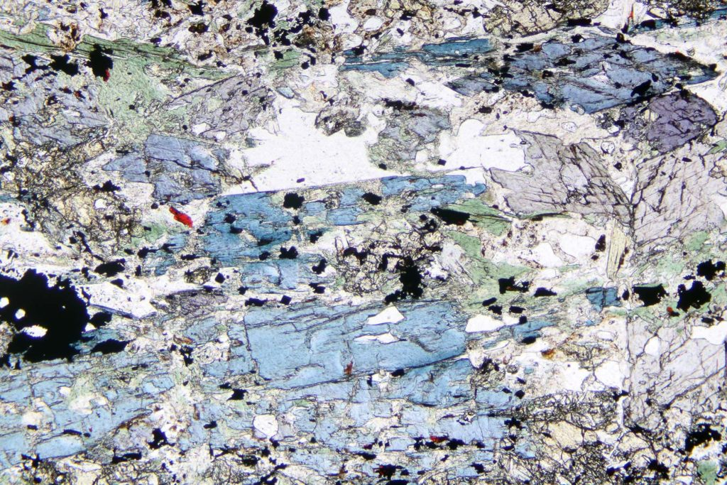 A blueschist thin section showing angular fractured shapes in green, blue, purple, white and gray.