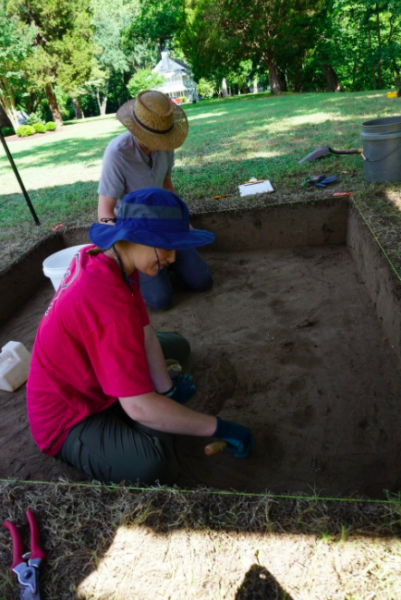 Two people in hats sitting in an excavation site made up of dark brown dirt surrounded by green grass.