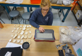 Mary Lawrence Young working on their computer at a large work table with a collection of shells next to them.