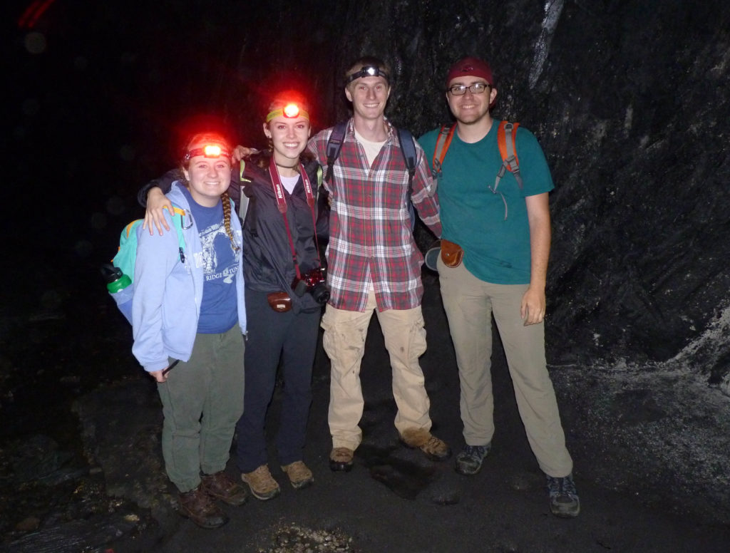 Four smiling geologists, posed with arms around each others' shoulders, in the dark, three with lit headband flashlights.