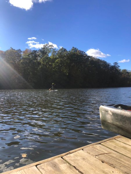 A person paddle boarding on Lake Matoaka taken on a wooden deck. The sky is blue with a few white clouds.