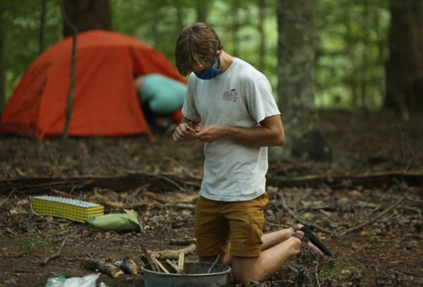 A masked student prepares a fire in a firepan, with a pitched tent and camper in the wooded background