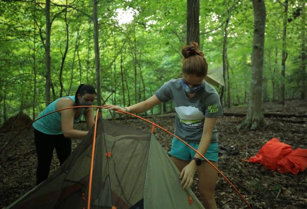 Two masked campers pitching their tent in the green woods of campus.