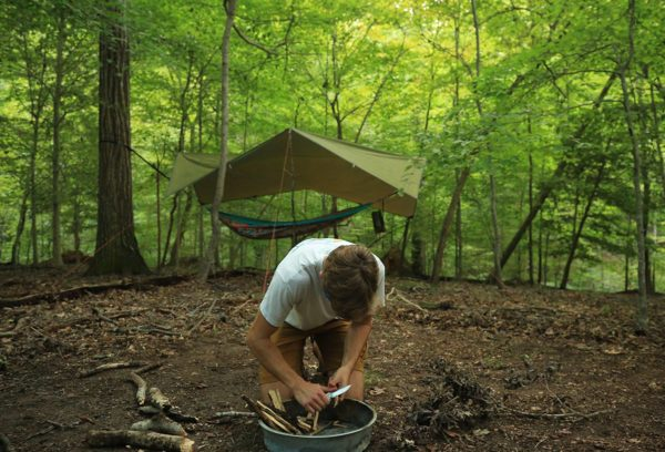A masked student prepares a fire in a firepan, with a hammock and its pitched cover in the wooded background