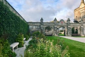 The quad at St Andrews in Scotland: lush green grass and bushes, with paths leading to grey stone arched walls