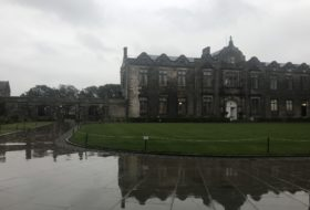 St Andrews Quad in Scotland. A stone building and its reflection on the wet ground, with a cloudy sky above.
