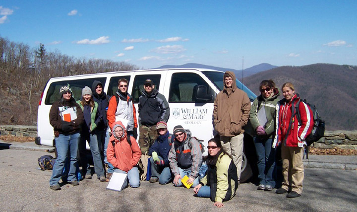 12 W&M geologists bundled in jackets, posed on the road side in front of a white van with a William & Mary Geology logo painted on the door, with wooded mountains and blue sky in the background.