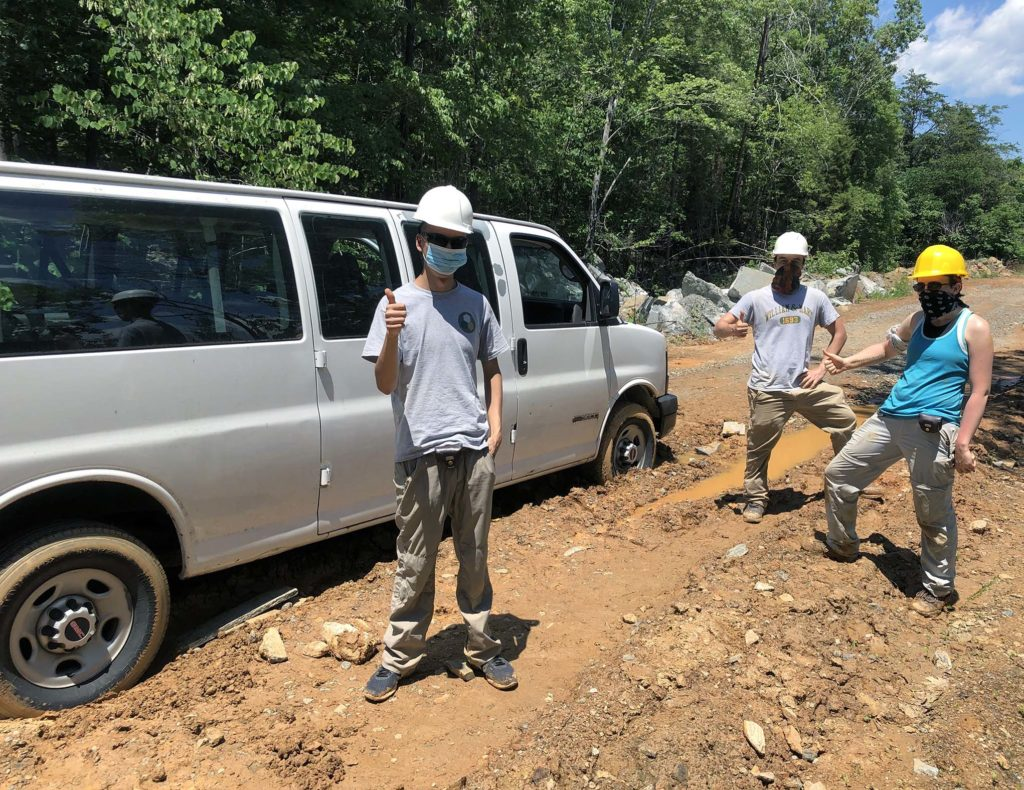 Geology van stuck in the mud with three masked and helmeted people giving a thumbs up.