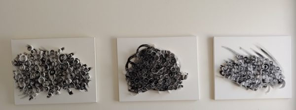 three canvases with black abstract shapes covered with many tightly packed curls of rolled paper