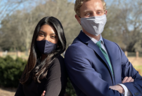 Two masked people, posed back to back with their arms crossed, in professional attire.